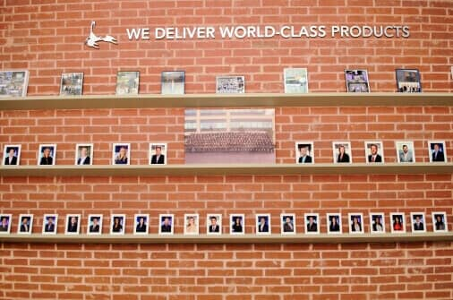 Image of brick wall with polaroid photos of Addison employees