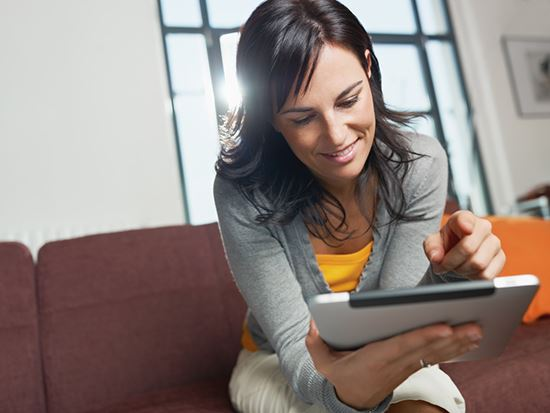 Woman sits on a couch and smiles while using her tablet.