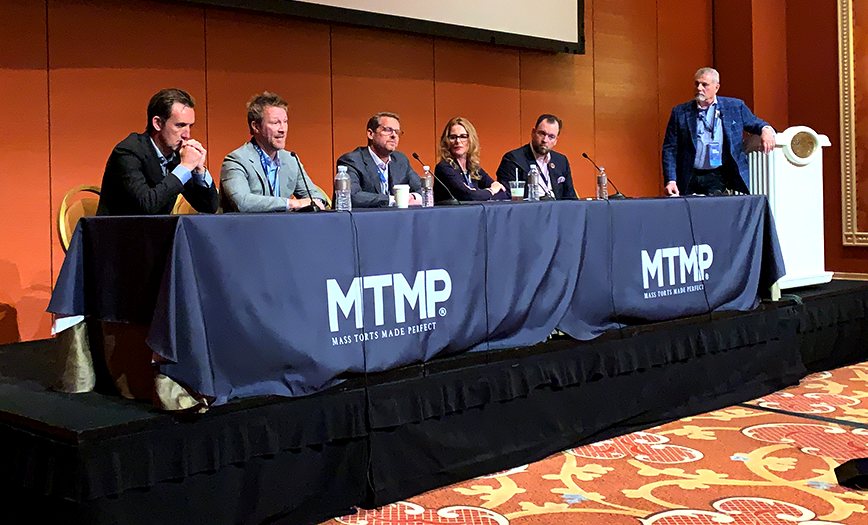 A panel of digital marketing experts sits at a table onstage in front of microphones, addressing the crowd at Mass Torts Made Perfect (MTMP).