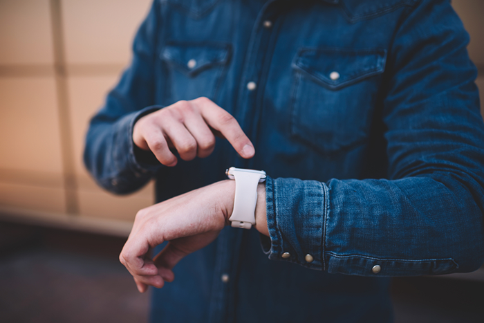 man in denim shirt using his smart watch