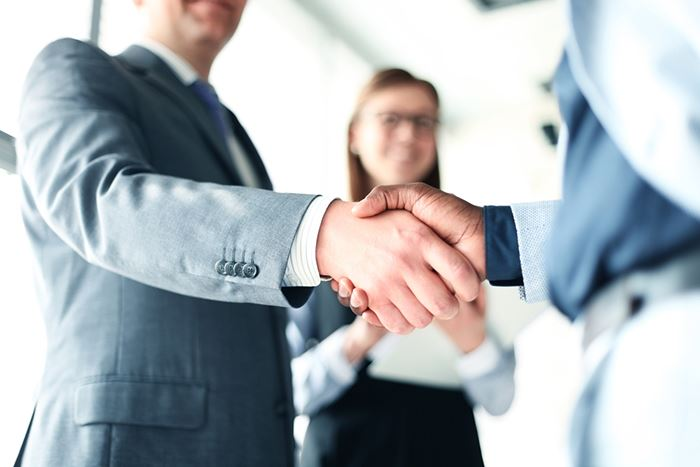 A man shaking the hand of another individual