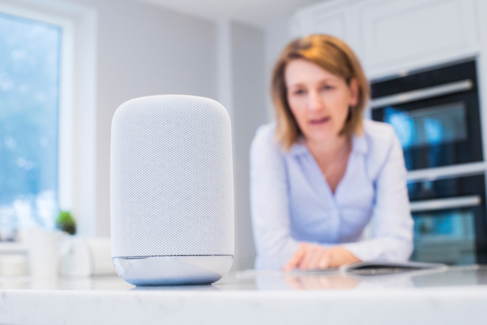 Woman standing at kitchen counter, speaking into a smart speaker