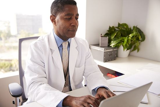 An image of a doctor on a laptop.