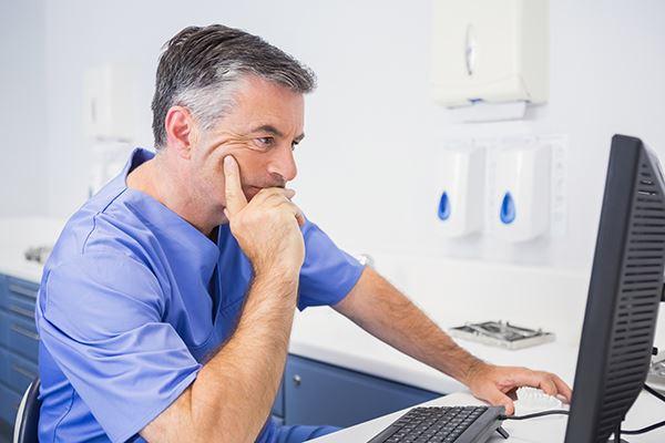 A displeased dentist looking online.