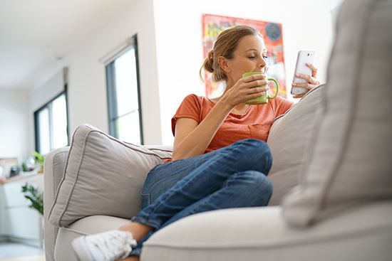 A woman looking on her phone while sitting on her couch at home.