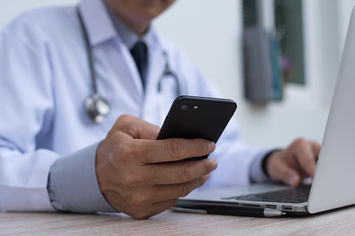 Doctor Using Phone and Laptop