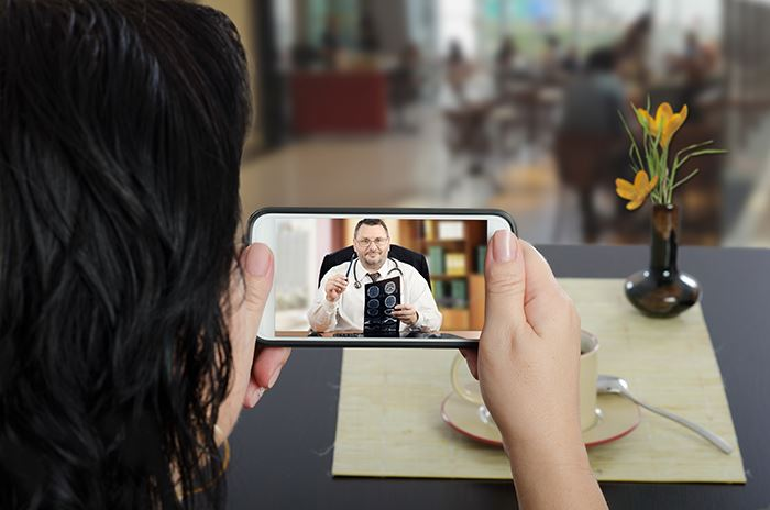 A woman watching a video on a smart phone of a doctor.