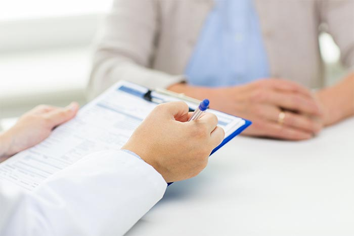 doctor writing notes on clipboard