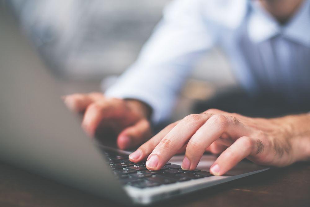 image of man typing on laptop