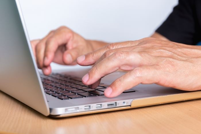 close-up of man typing on laptop